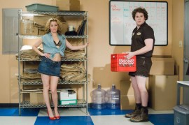 Miri is looking hot in red heels, a denim skirt and her shirt tied open to reveal a black bra. Zack looks ridiculous in a postal workers outfit of brown shirt, shorts and boots