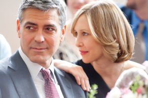 An image from Up in the Air of Clooney and Farmiga; she has her hand on his shoulder as both look towards the left