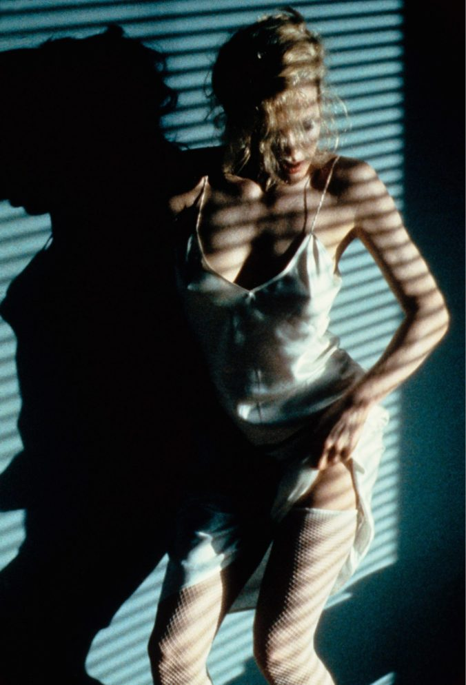 An image from Nine 1/2 Weeks showing Elizabeth stripping in the stripes of a Venetian blind