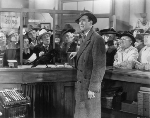 An image from It's a Wonderful Life showing George in the Buildings and Loan Company, surrounded by people and looking lost