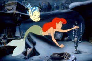 An image from The Little Mermaid of Ariel looking at human artefacts