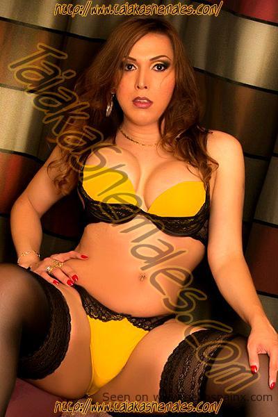 Sensual trans desnuda en ropa femenina negra y amarilla.