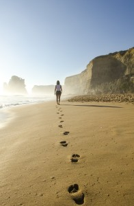 Image: a woman in shorts and a top walking away from the camera on a beach, her footprints in the sand behind her.