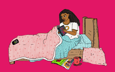 Young woman reading a book in her bed.