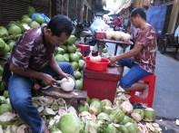 Couple of dudes preparing coconuts to sell for drinking. You can see the prepared ones on the table in the background.