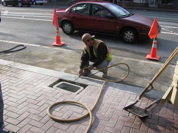 An SFMTA worker installs a counter on Market Street near Van Ness.