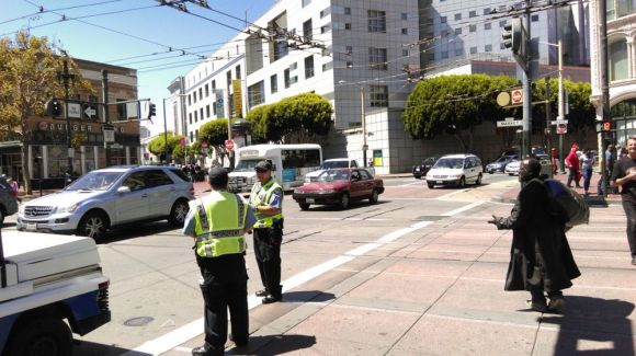 SFMTA parking control officers posted to instruct drivers not to turn on to Market at Eighth Streets. Photo: Aaron Bialick