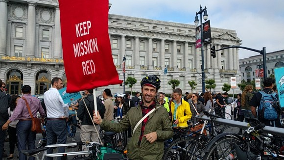 Anthony Ryan displays a banner from a Transit Riders campaign to keep transit-only lanes on Mission. Photo: Streetsblog.