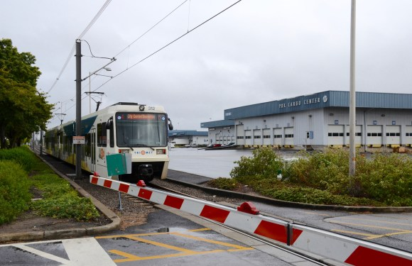 A Portland MAX train crossing an intersection. Railroad crossing gates could give the M-Ocean View all the speed advantages of a subway tunnel without any of the costs. Image: Wikiemedia commons.