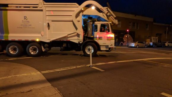 "A garbage truck is forced to make a slow, careful turn, rather than sweeping the corner and potentially running over a cyclist in its ""blind"" spot. Photo: Streetsblog"