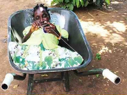 Ekolu pushing his daughter, Atim, in her wheelbarrow