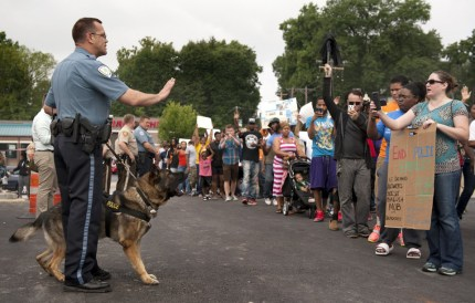 While the Jackie Robinson West Little Leaguers have won America's heart, those boys would be treated in any hood in the country no better than 18-year-old Michael Brown – and these parents know it as they confront cops with snarling attack dogs on Aug. 10 in Ferguson, Missouri. – Photo: Sid Hastings, AP