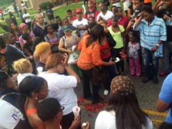Michael Brown's grieving mother spreads flowers on the street where her son was shot and killed by police in Ferguson, Mo. – Photo: John Kelly, KSDK