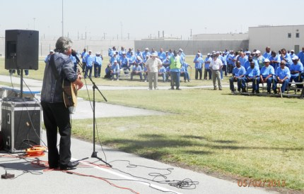 """CSATF prisoners listen to a visiting missionary in the """"hot flaming sun"""" of the San Joaquin Valley. For prisoners whose color has faded from decades in isolation, with rare exposure to sunlight, the hot sun of the San Joaquin Valley is good medicine."""