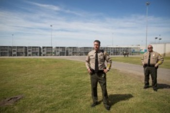 "Officers Vickjord and Mayo stand guard in the ""exercise yard"" for prisoners in the SHU – one prisoner to each cage. – Photo: Grant Slater, KPCC"