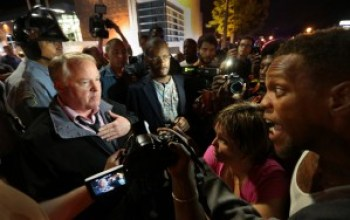 """In a story headlined, """"Ferguson Police Chief March Backfires,"""" The Daily Beast reports: """"Hours after issuing an apology to the family of Michael Brown, Ferguson Police Chief Thomas Jackson attempted to march with protesters, many of whom are calling for his resignation. … 'I don't think he was marching with the protesters more than 30 seconds before the riot cops came out into the crowd and tried to get themselves closer to him and protect him, said Antonio French, a St. Louis elected official."""" Brutal arrests ensued. – Photo: Robert Cohen, St. Louis Post-Dispatch"""