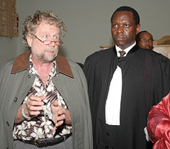 "International criminal defense attorney Peter Erlinder – in handcuffs for ""genocide denial"" – appears in a Kigali, Rwanda, courtroom with Kenyan lawyer Kennedy Ogetto in May 2010."