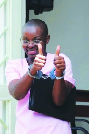 """Victoire Ingabire, despite being in handcuffs for """"genocide denial,"""" gives a thumbs up to her supporters outside a Rwandan courtroom on April 17, 2012."""