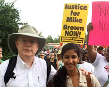 Bill Quigley, former legal director of the Center for Constitutional Law, marches in Ferguson with Meena Jagannath, Ella Baker site coordinator for Florida Legal Services. – Photo: CCR
