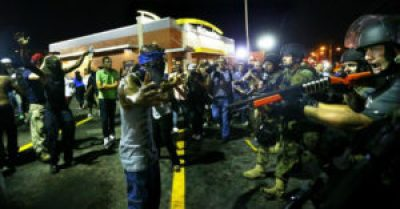 """""""Police officers move in to arrest protesters as they push and clear crowds out of the West Florissant Avenue area in Ferguson, Mo., early Wednesday, Aug. 20,"""" reads the AP caption. – Photo: Curtis Compton, Atlanta Journal-Constitution"""