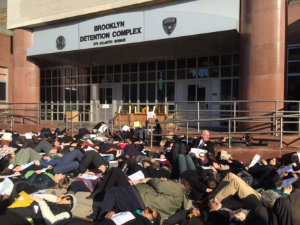 """Over 200 public defenders stage a """"die-in"""" in front of the Brooklyn Detention Center. They lay on the concrete for seven minutes, the length of time a bystander's video shows Eric Garner lay on the ground not breathing. For the final minute, the group fell silent. – Photo: Lauren Gambino"""