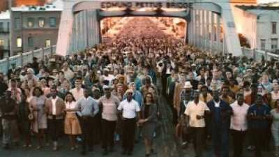 """In a scene from the new movie, """"Selma,"""" marchers finally, with Dr. King in the lead, cross the Edmund Pettus Bridge out of Selma on their way to Montgomery, their numbers growing as they walked. On their first attempt to cross the bridge, John Lewis and others were nearly beaten to death."""