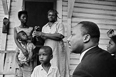 "After passage of the Civil Rights Act, Dr. Martin Luther King Jr. focused on economic racism. He learned how people – urban and rural – cope with deep poverty by visiting them, often staying as a guest in their home for a time. Here he visits a family in Greenwood, Miss., in July 1964. When he died, he was finalizing plans for the Poor People's Campaign. But that work is far from finished. The Black poverty rate in 2011 was almost as high as in 1969, the year after King was assassinated. Dr. King said, ""America is going to hell if we don't use her vast resources to end poverty and make it possible for all of God's children to have the basic necessities of life."" – Photo: Jim Bourdier, AP"