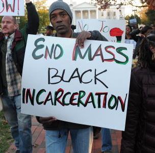 'End Mass Black Incarceration' Black man holding sign at protest