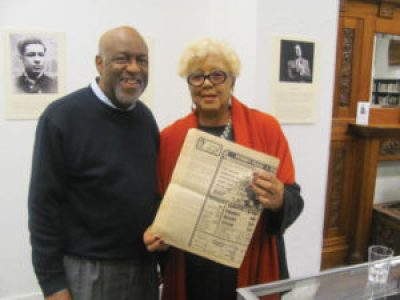 "Keynoter Rochelle Metcalfe holds a historic copy of the Sun Reporter turned to her ""I Heard That,"" a must-read in the Black community for 32 years, as she chats with San Francisco African American Historical and Cultural Society President Al Williams at the Society's popular annual Black History Month reception, held this year on Feb. 20."