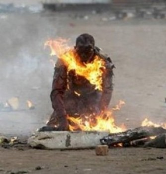 The victim of a xenophobic petrol bomb attack burns to death on the street.