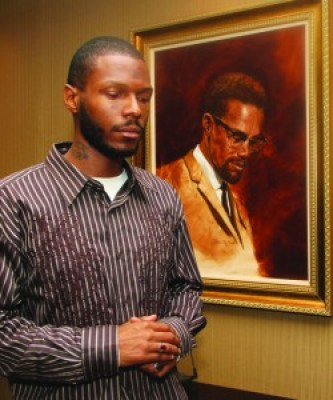 After being interviewed by the Los Angeles Sentinel, a major Black newspaper, Young Malcolm stopped to pay tribute to his grandfather, Malcolm X, whose portrait hangs in the Sentinel offices. – Photo: LA Sentinel