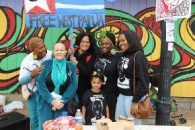 """The cry to """"Free West Papua"""" was a major part of the Malcolm X Day celebration in Hunters Point on Sunday, May 17, at Kenneth Harding (Mendell) Plaza, renamed by the people for Kenny, who was murdered there by SFPD in 2011. From left are Angela Naggie, mother of 2014 SFPD murder victim O'Shaine Evans; Mesha Irizarry, mother of 2001 SFPD murder victim Idriss Stelley and one of the main organizers of the very successful event; Free West Papua advocate Loa Niumeitolu; and Cadine Williams, sister of O'Shaine Evans, accompanied by her little daughter and younger sister. Loa made a powerful presentation, calling on everyone to support the West Papuan freedom fighters – Jeremy Miller reminding the crowd that Malcolm X preached pan-African solidarity."""