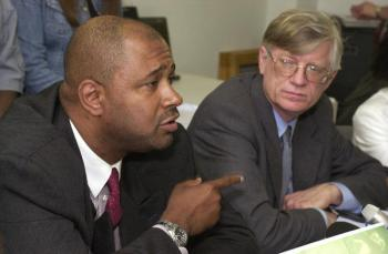 "In this June 26, 2003, news conference, former death row inmate Aaron Patterson and attorney G. Flint Taylor of the People's Law Office announced a lawsuit filed for his wrongful imprisonment. Taylor began representing Patterson, who'd been convicted of a double murder but had used a paper clip to crudely scratch a message on a police station bench saying: ""Aaron I lie about murders, police threaten me with violence ..."" As Patterson's case was being appealed, then-Gov. George Ryan, days from leaving office, commuted the sentences of everyone on death row. He'd already halted executions when 13 inmates were found to have been wrongly convicted. – Photo: Jim Frost, Chicago Sun-Times"