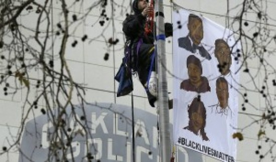A Black Lives Matter protester climbs the flagpole outside Oakland PD headquarters on Dec. 15, 2014.