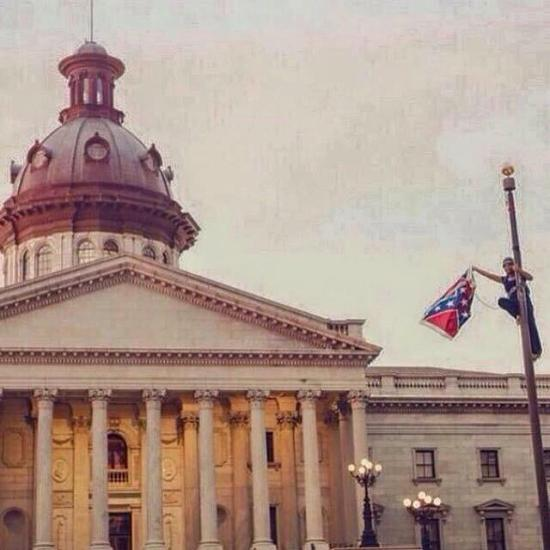 Bree Newsome climbs the 30-foot flagpole on the South Carolina capitol grounds June 27, 10 days after the massacre at Mother Emanuel, unhooks the Confederate battle flag and brings it down. Though the flag was replaced an hour later, only 12 days later, the Legislature voted it down for good. – Photo: Joshua Thicklin