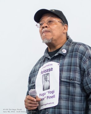 At the Rally for Yogi, Willie Sundiata Tate speaks about his comrade, Hugo Pinell, pictured on the flier pinned to his shirt. – Photo: Scott Braley