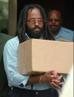 Handcuffed, Mumia carries a box out of the courthouse after a hearing in 1995. He survived at least two execution dates.
