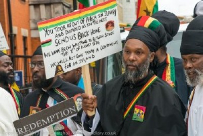 On the centenary of the foundation by Marcus Garvey of the Universal Negro Improvement Association, Aug. 1, 2014, Rastafaris met at Brixton in London to march to Parliament demanding reparations for the descendants of those taken from Africa by the Atlantic Slave Trade. Their sign's mention of Aug. 1, 1834, refers to Emancipation Day, when slavery was ended in the British Empire.