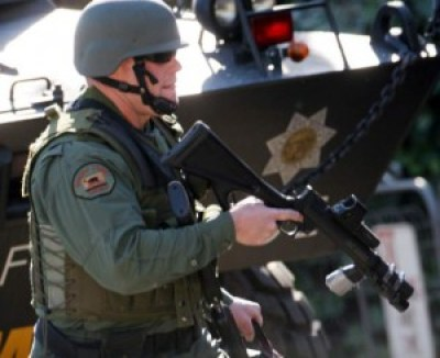 """A Sonoma County sheriff's deputy, part of a SWAT team, stands in front of the Sheriff's Department's huge tank, or """"armed personnel carrier."""" Sonoma County, in California's wealthy wine country, is heavily militarized. – Photo: Santa Rosa Press Democrat"""