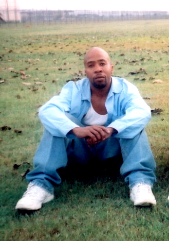 Curtis Ray Davis II sits in the grass on the 18,000 acre former slave plantation known as Angola, the largest maximum security prison in the U.S., where the prisoners, 80 percent of them Black, work the fields just as their ancestors did.
