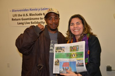The People's Minister of Information JR Valrey and Cuban National Assembly member Kenia Serrano display a copy of the Bay View, the paper where their interview will appear. – Photo: Kali O'Ray