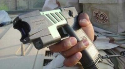 A police officer holds a Taser, also known as a stun gun or ECW.