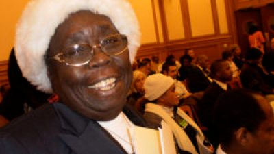 Espanola Jackson, veteran of countless City Hall showdowns on the fate of her people, smiles to encourage the younger folks at a hearing on the environmental impact report on the Hunters Point Shipyard on Dec. 17, 2009. At the behest of developer Lennar, the supervisors approved it despite the shipyard's status as one of the most contaminated places in the country. But with Espanola's encouragement, the community fights on. – Photo: Carol Harvey