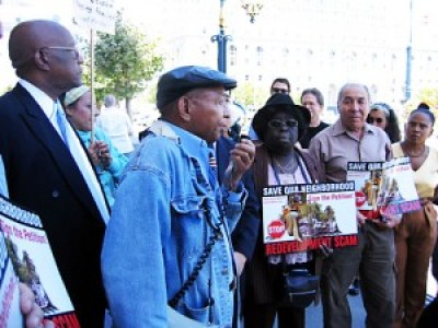"When the Redevelopment Agency tried to take control of Bayview Hunters Point, the community gathered 33,000 signatures on a referendum, turning them into City Hall with a ""Redvelopment RIP"" ceremony on the steps. Referendum campaign leaders include Willie Ratcliff on the mic, Charlie Walker, Espanola Jackson and Ahimsa Sumchai. – Photo: Francisco Da Costa"