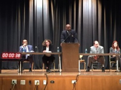 "Troy Williams speaks as the other members of the Department of Justice ""listening session"" panel sit on the stage of the Thurgood Marshall High School auditorium on Feb. 24. – Photo: Hoodline"
