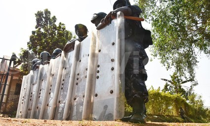 """Policemen barricade the home of Dr. Kizza Besigye in Kasangati on Tuesday, Feb. 23. """"We have information that he (Besigye) was planning to cause an insurrection against an elected government. That is treasonous because he will be fighting the Constitution,"""" said Police Assistant Inspector General Felix Kaweesi. The move to silence Besigye came when he tried to announce his party's vote count in the Feb. 18 election. – Photo: Roderick Ahimbazwe"""