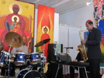 Archbishop Franzo King, beloved activist and courageous spokesperson for the Black community, plays saxophone a la John Coltrane with the Ministers of Sound in the world renowned St. John Coltrane Church he founded 48 years ago. – Photo: mswine, Flickr