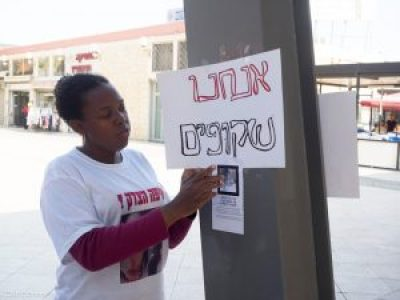 "Local activist posts flyer about Toveet Radcliffe and a placard reading ""We are invisible,"" referencing a recently popularized working class protest slogan. – Photo: Dan Cohen"