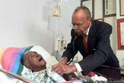 Dr. Coleman made house calls nearly till the day he died. Here, at the age of 81, he visits his friend and another pillar of Bayview Hunters Point, Sam Jordan. – Photo: Carlos Avila Gonzalez, SF Chronicle