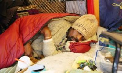 "Markale Raybon, Gongora's best friend, sleeps in his tent. According to the London Guardian, he said of Gongora's murder: ""'We were just hanging out right here smoking pot, and then he walked up the street kicking the ball. The next thing I knew, I heard the throttle of a car, and then I heard someone shouting, and the shots.' … 'He was my brother. He called me ""hermano"".'"" – Photo: Dan Tuffs, The Guardian"